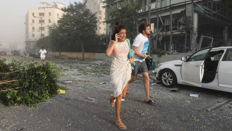 """People run for cover following an explosion in Beirut""""s port area, Lebanon August 4, 2020"""