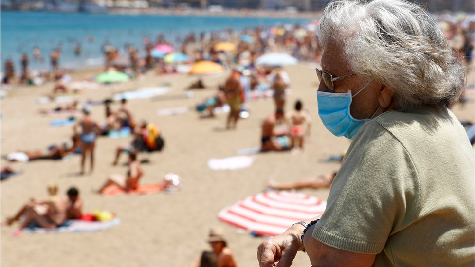 A woman wearing a face mask watches people sunbathing on the Las Canteras beach as some Spanish provinces are allowed to ease lockdown restrictions during phase two, amid the coronavirus disease
