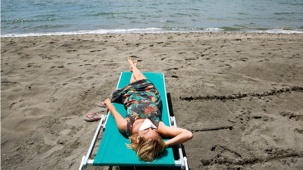 "A woman wearing a face mask sunbathes at the beach after it officially reopened for the first time following the country""s strict coronavirus disease (COVID-19) lockdown, in Fregene, near Rome, Italy,"