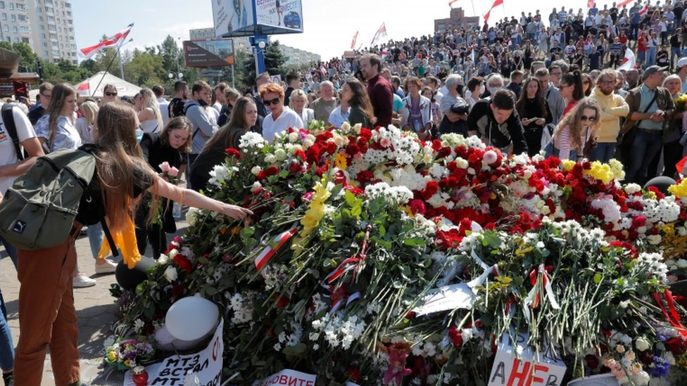 People place flowers at a makeshift memorial on Saturday