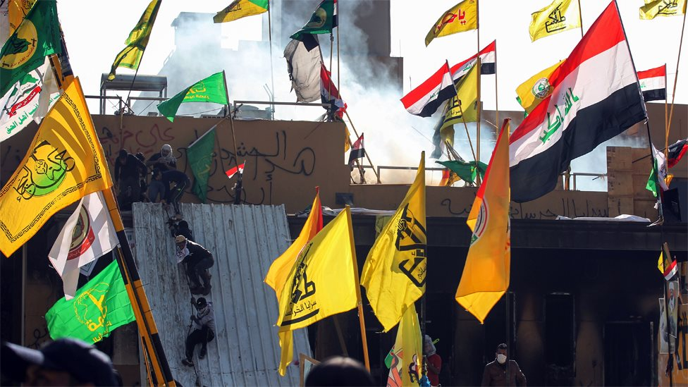 Supports of Iraqi militias climb onto the outer walls of the US embassy in Baghdad during a protest on 1 January 2020