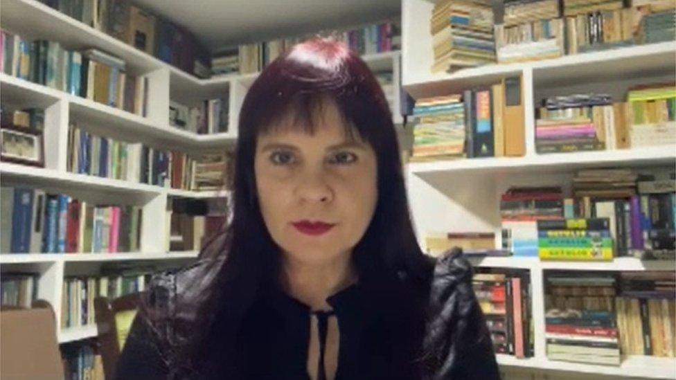 Médica Melania Amorim olhando em direção a computador em sala repleta de estantes e livros