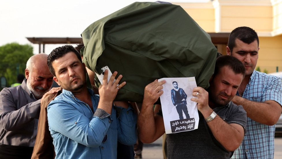 Iraqi Kurdish men carry the coffin of a Kurdish migrant, who died in a lorry in Austria alongside other migrants in 2015