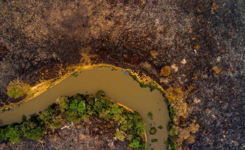 A drone shows scorched earth next to a river