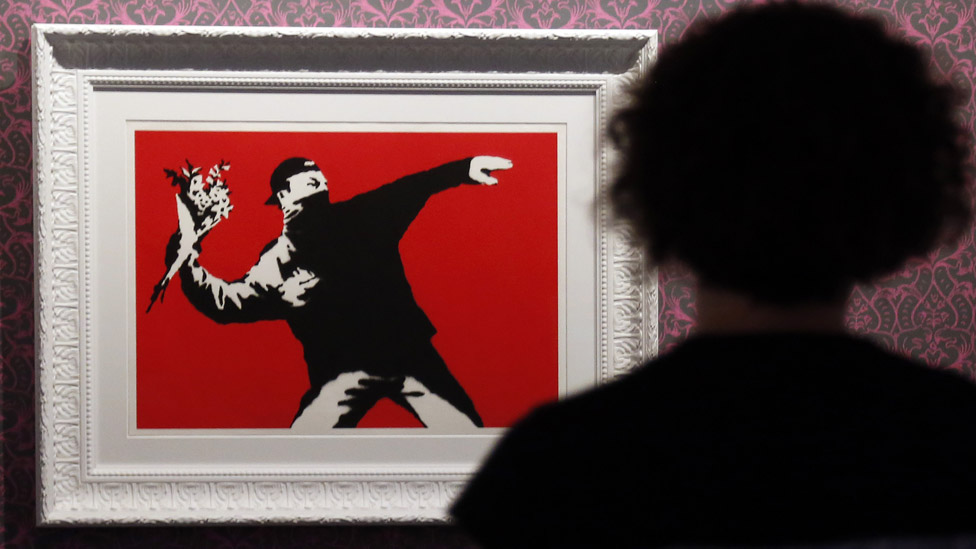 Woman looking at Banksy's flower bomber
