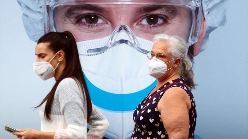 People, wearing protective face masks, walk past a dental clinic advertisement at Vallecas neighbourhood in Madrid, Spain, September 18, 2020.