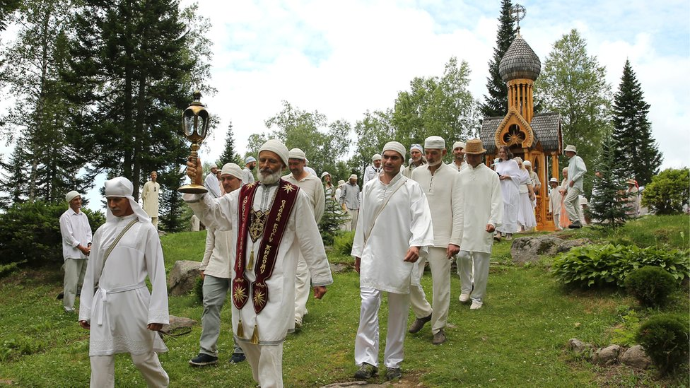 Followers of the Church of the Last Testament religious movement walk after a religious service
