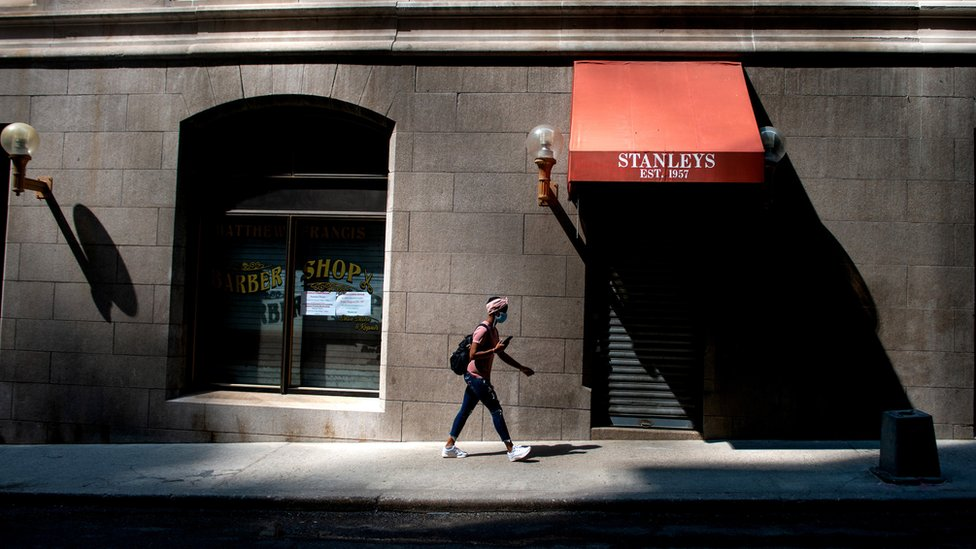 A woman, wearing a face mask, walking down a New York street and a barber's with the shutters down