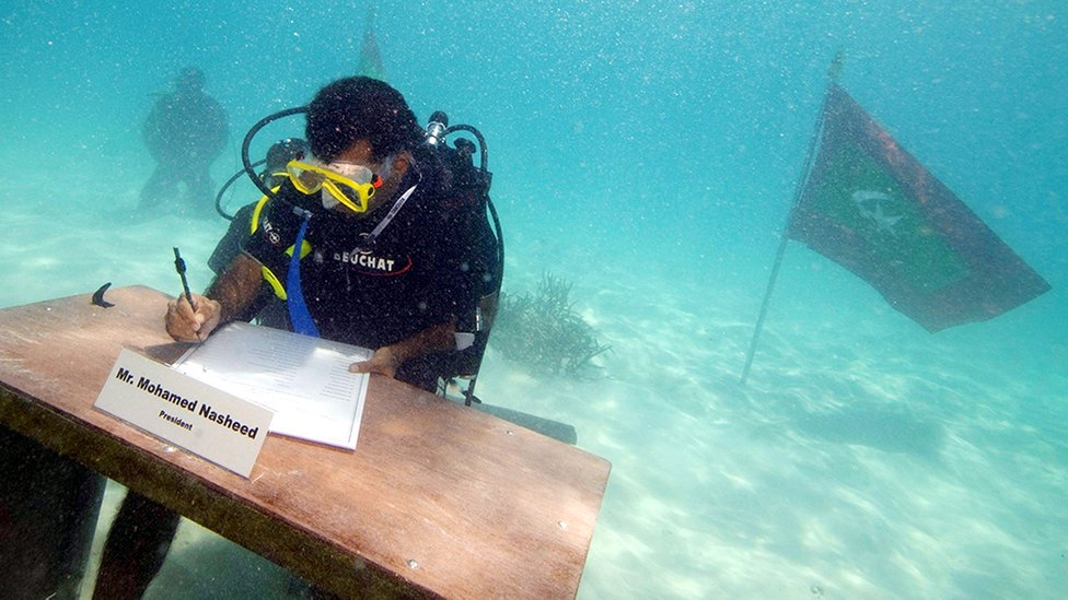 Maldives President Mohamed Nasheed, seen signing a paper while wearing diving gear.
