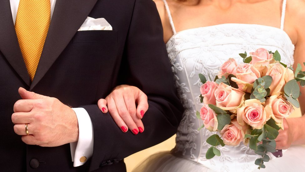 Bride linking arms with groom