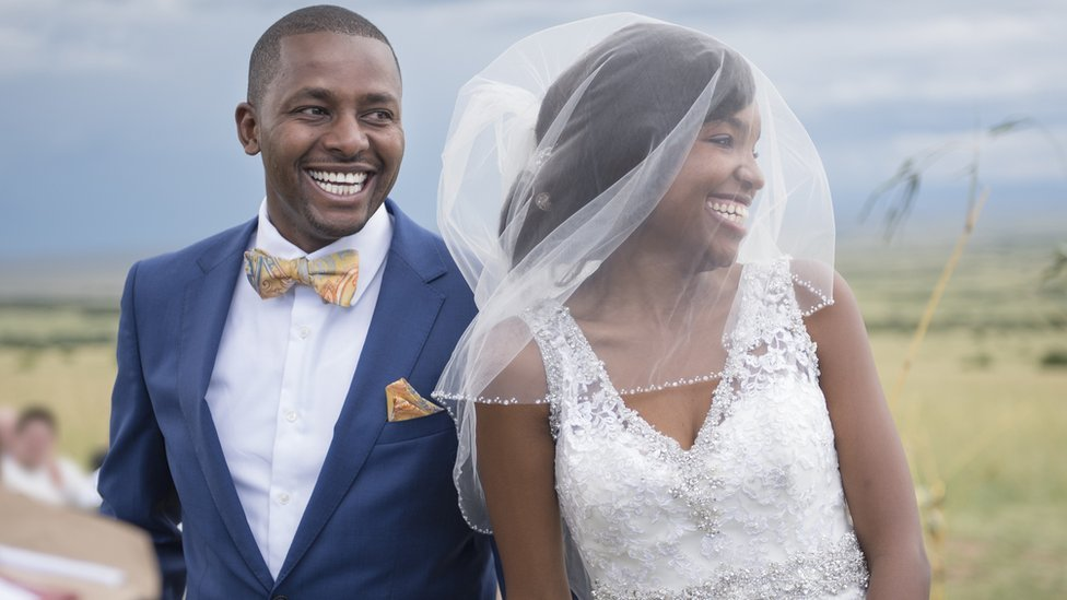 Smiling bride with veil and groom