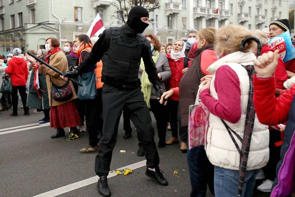 Belarusian pensioners argue with a law enforcement officer during a rally to demand the resignation of Alexander Lukashenko and new fair election in Minsk on 12 October 2020