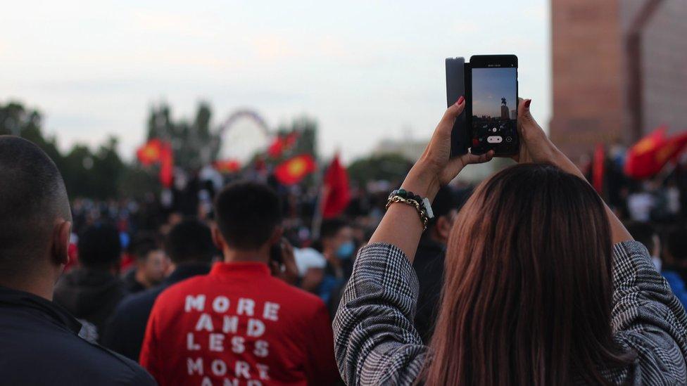 Protestuющaя fotografiruet demonstrantov