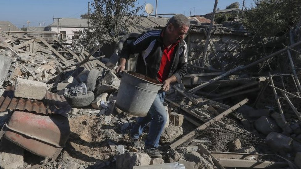 A man removes debris from shelling in the Nagorno-Karabakh capital, Stepanakert