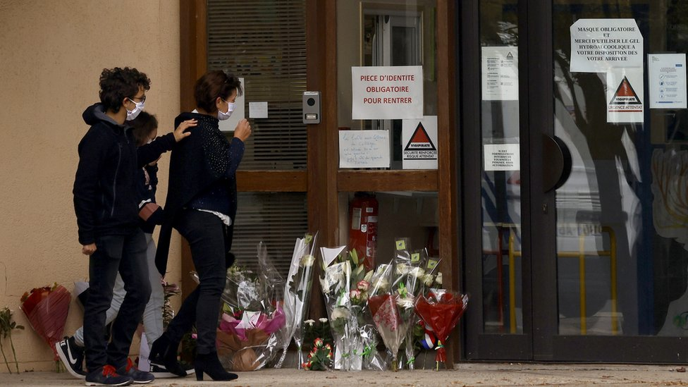 Parents and children lay flowers outside the school after teacher Samuel Paty was beheaded