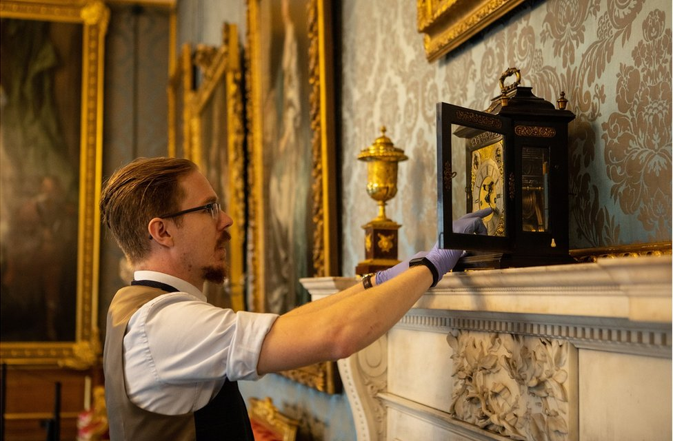 A close-up of Fjodor changing the time on a clock in a state apartment