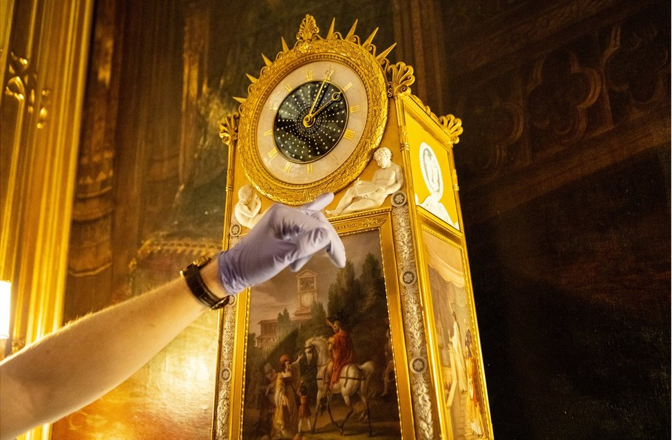 Fjodor points to a beautiful clock that features cherubs and panel paintings