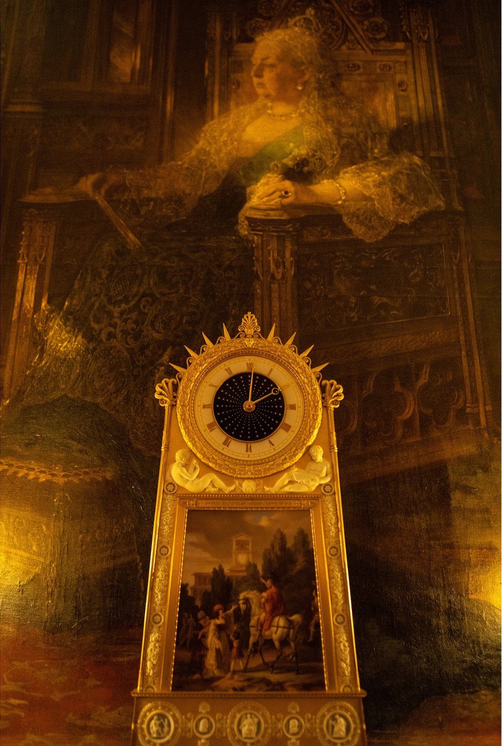A beautiful clock with a large portrait of Queen Victoria behind it