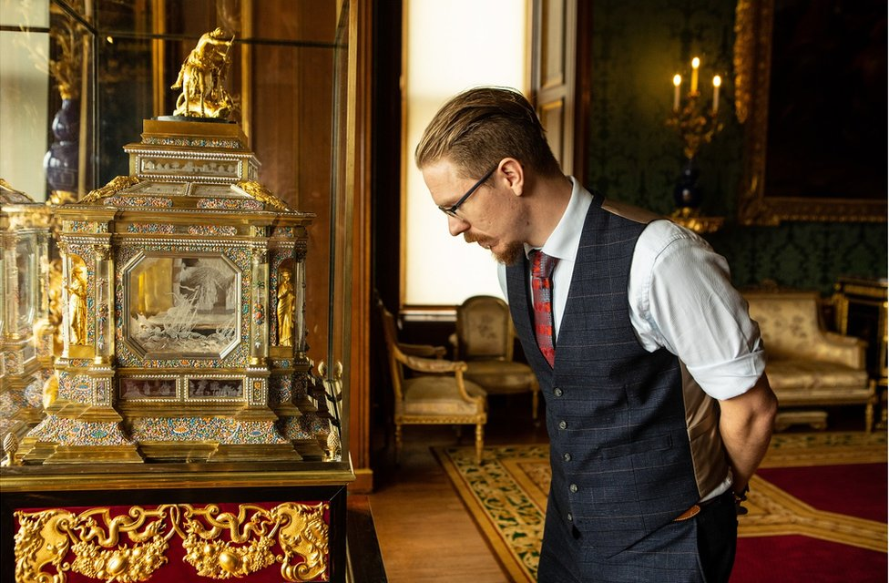 Fjodor looks at the casket of the an organ clock