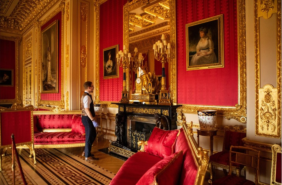 Fjodor stands in a large gold and red state apartment