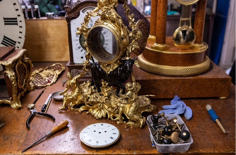 A clock case on a work bench surrounded by tools