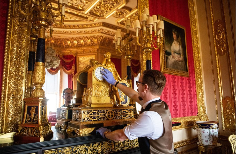 Fjodor changes the time on a clock in the Crimson Drawing Room