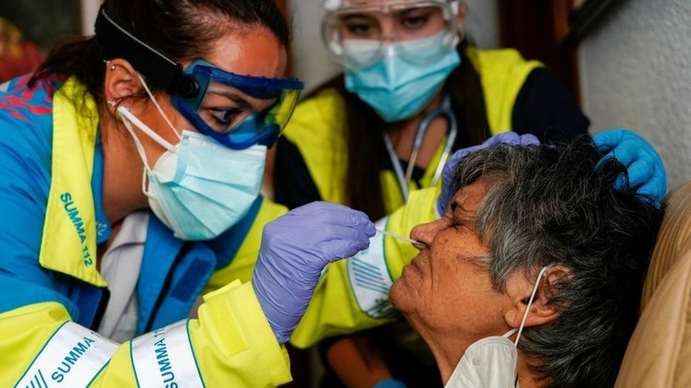 A medic tests an elderly woman for Covid-19 in Madrid