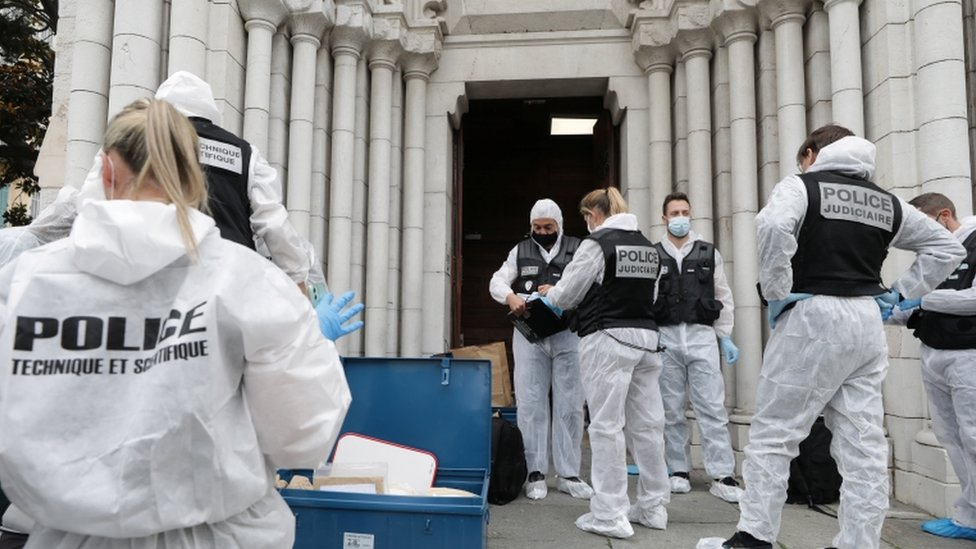 Forensic specialists stand at the entrance to the Notre Dame church in Nice