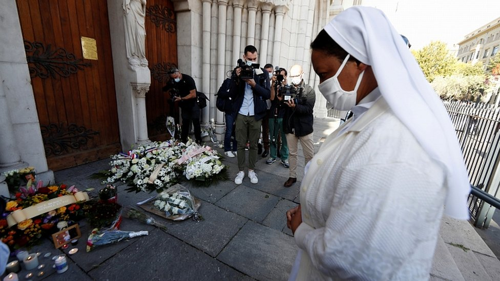 A nun prays in front of candles and flowers left in tribute to the victims of a knife attack at the Notre Dame church in Nice, France, October 30, 2020