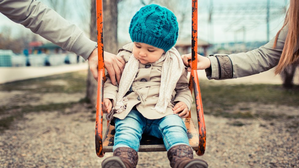Child on a swing in between her parents