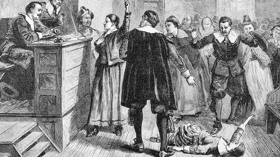 A girl is depicted on the floor during a witch trial in Salem