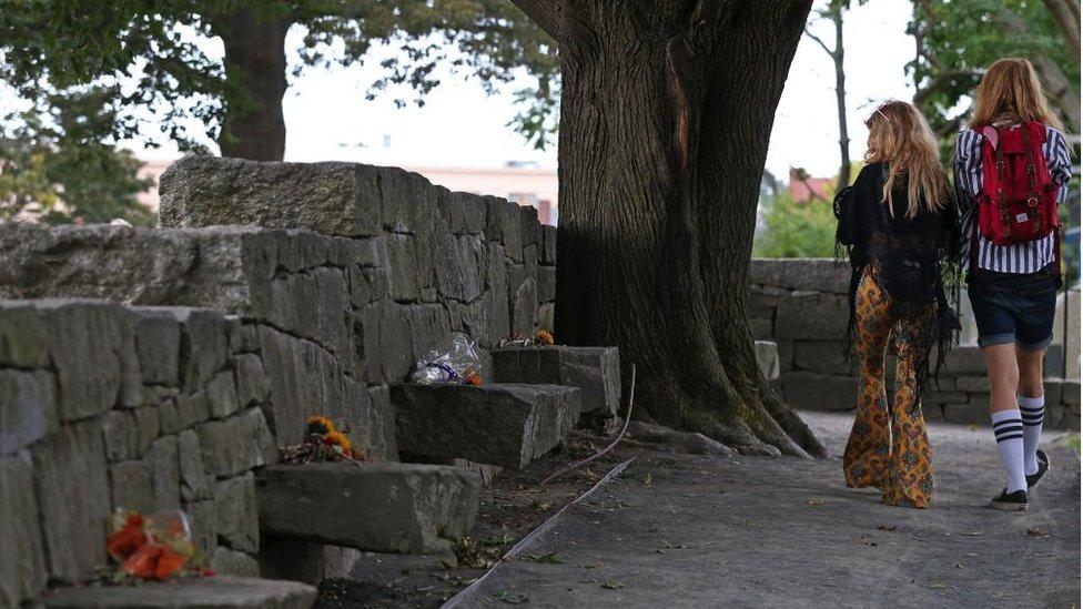 Visitors walk through the Salem Witch Memorial in Salem, Massachusetts on Sep. 26, 2019