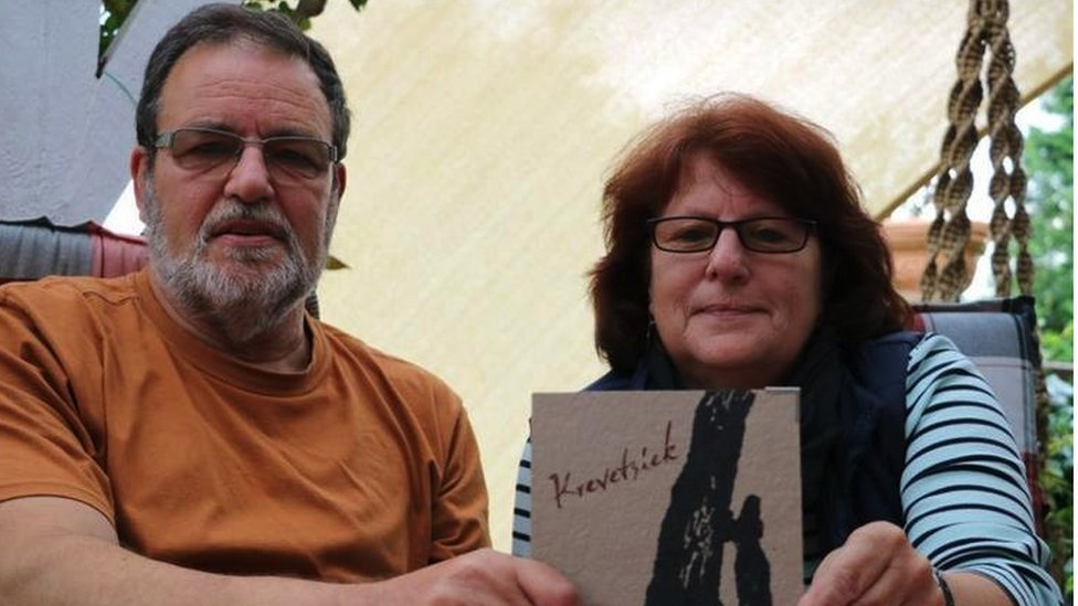 Bernd and Ulla Brammer hold a booklet showing the name of their ancestor 'witch'