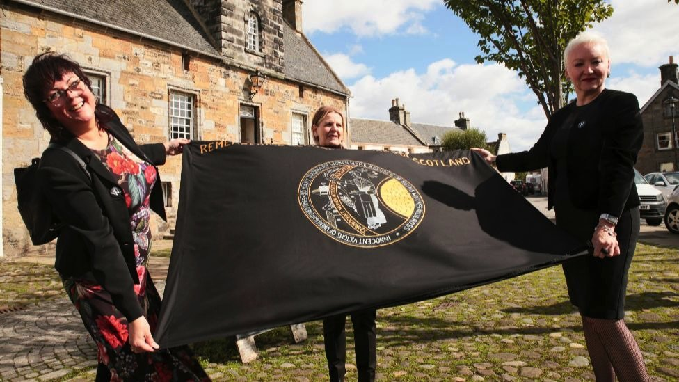 """Campaigners in Culross, Scotland, holding a flag that reads, """"Remembering accused witches of Scotland@"""