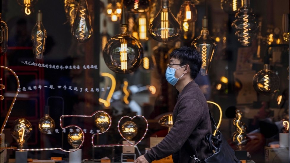 A man wearing a mask for protection walks in front a shop window selling bulbs and lighting in Shanghai, China