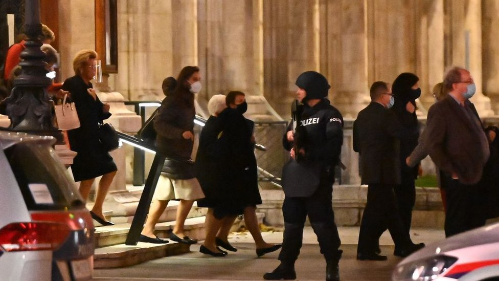 Opera guests leave the state opera under the supervision of armed policemen, in the centre of Vienna on November 2, 2020