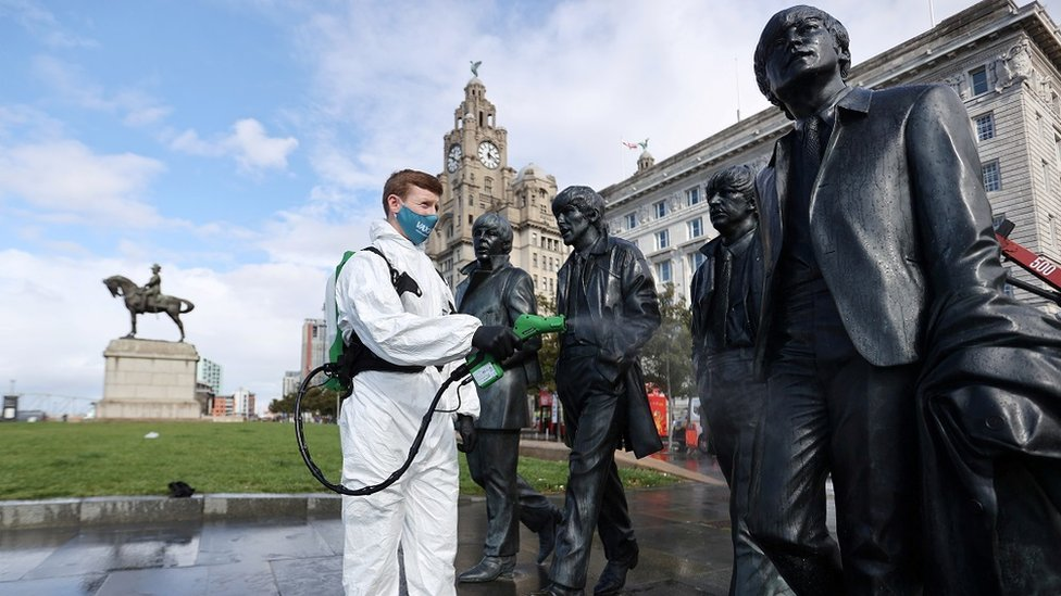 A man wearing a face covering cleaning statues of the Beatles
