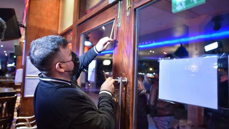 A worker shuts the doors in a bar in Bristol city centre, ahead of a national lockdown for England from Thursday