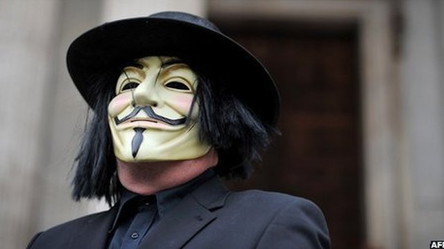 A masked protestor stands on the steps of St Paul's Cathedral in London