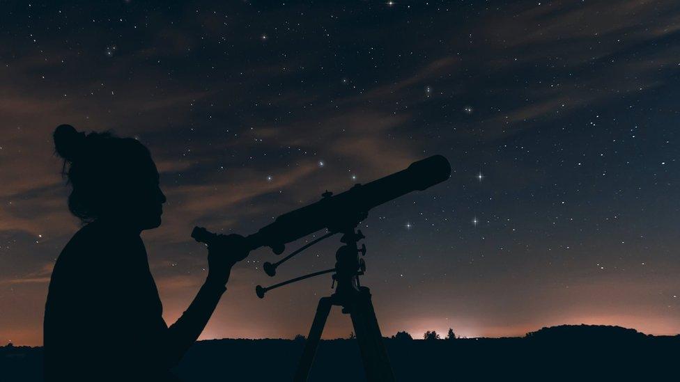žena gleda kroz teleskop