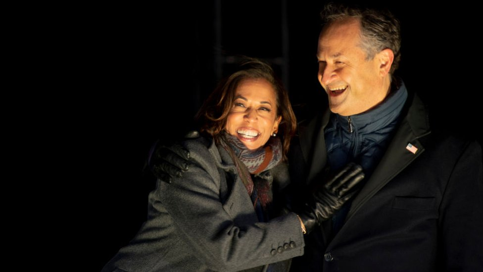 Democratic vice presidential nominee Sen. Kamala Harris (D-CA) and husband, Douglas Emhoff, embrace on stage after Democratic presidential nominee Joe Biden spoke in Pittsburgh at a simultaneous drive-in election eve rally on November 2, 2020 in Philadelphia, Pennsylvania