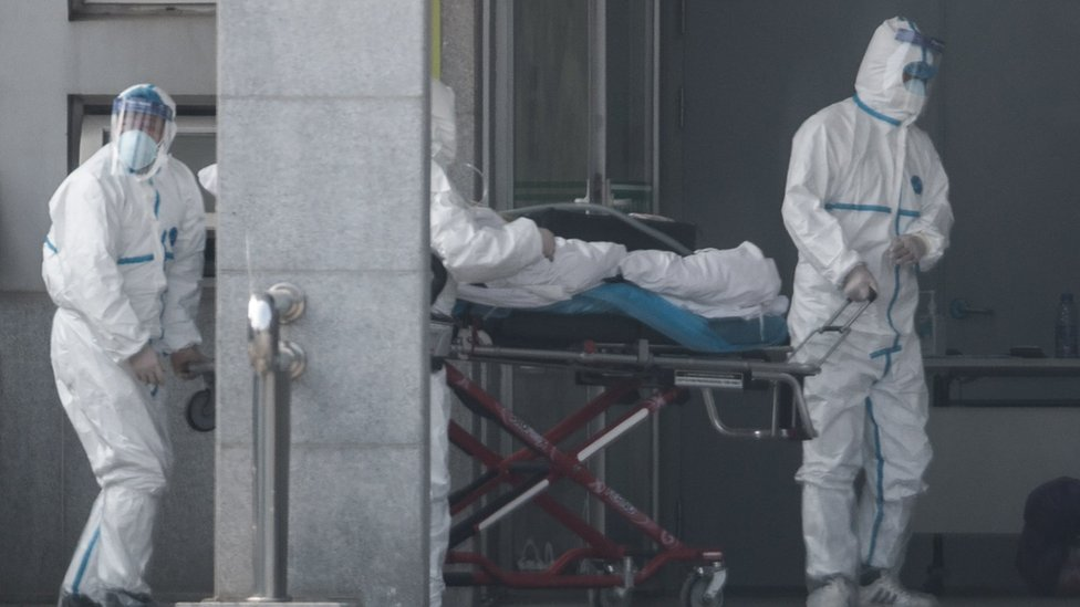 Medical staff carry a patient into the Jinyintan hospital in Wuhan on 18 January 2020.