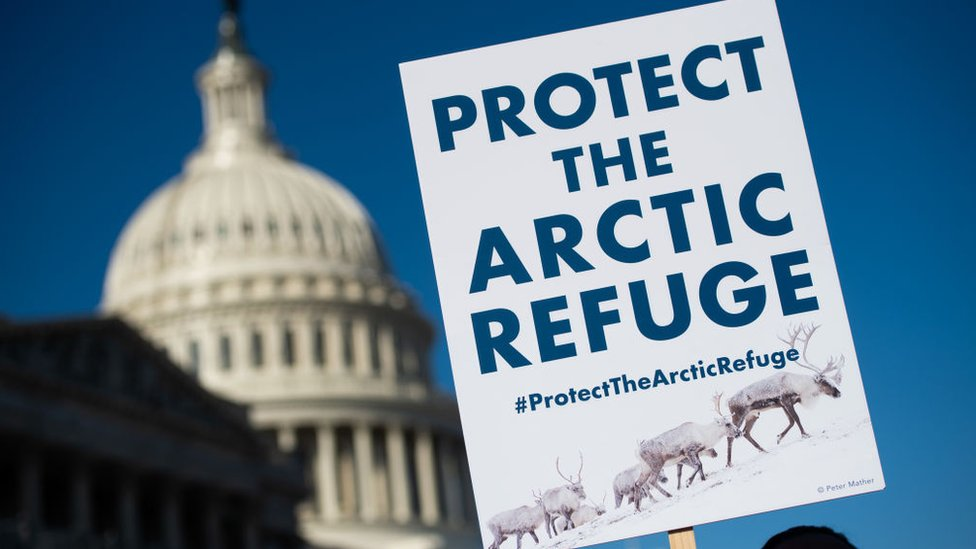 A demonstrator holds a sign against drilling in the Arctic Refuge on the during a press conference outside the US Capitol