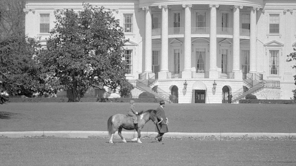 With a Secret Service man leading the way, Caroline Kennedy, the President's daughter, takes a ride on her pony, Macaroni, in 1962