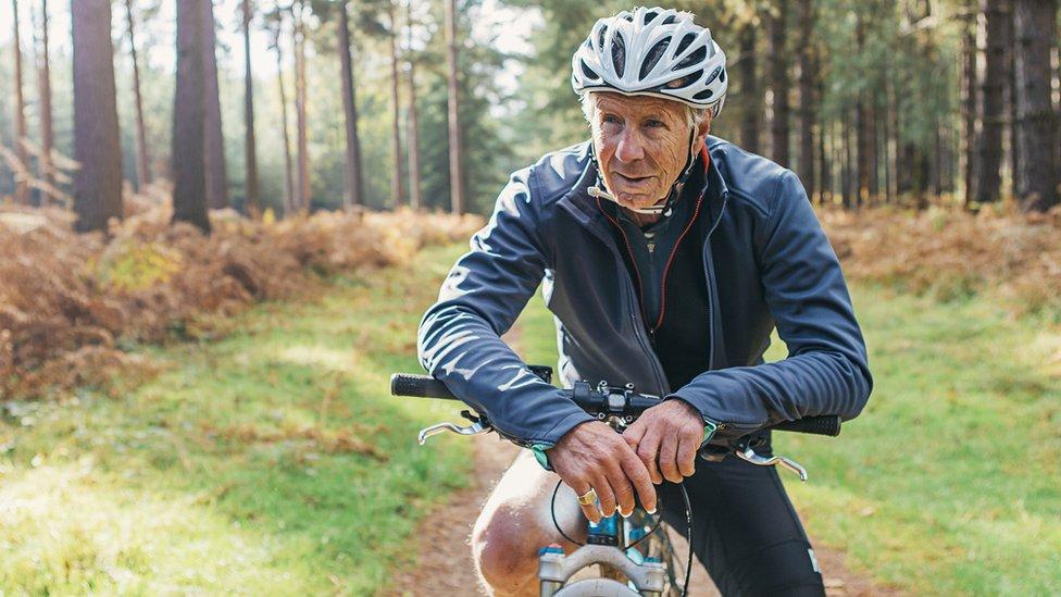 stariji muškarac za biciklom