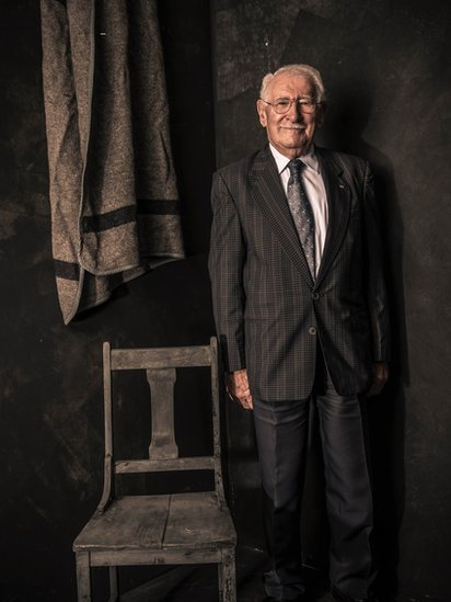 Portrait of Eddie Jaku with a chair and a blanket like the ones he used to have in Auschwitz