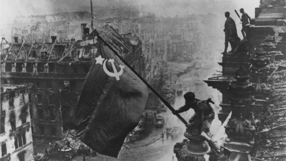 Russian soldiers flying the Red Flag over the ruins of the Reichstag in Berlin.