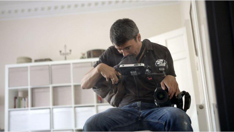 Xavier Alford holding his camera