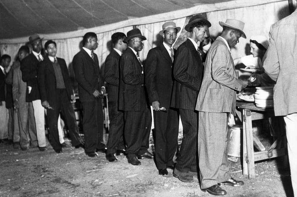 Jamaican men in Britain to look for work, line up in a canteen marquee to get a meal, 1948