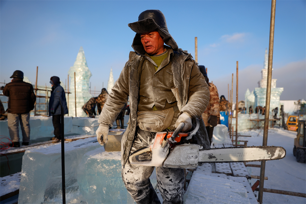 A worker carries a chainsaw while constructing an ice structure